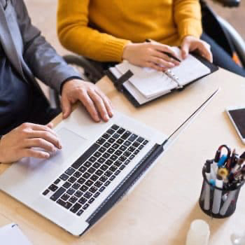 Man and woman sitting at desk for business consulting.