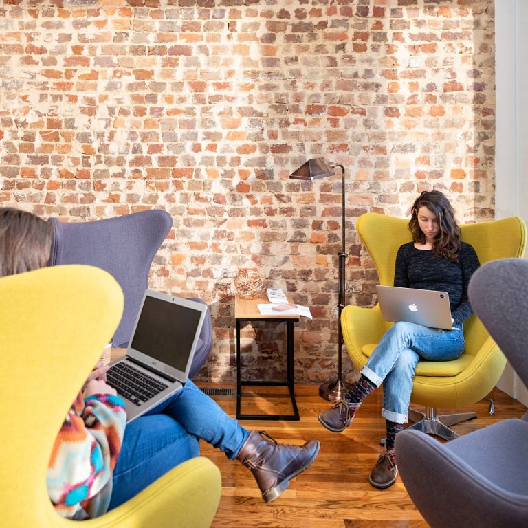 Two women working on laptops in coworking space.