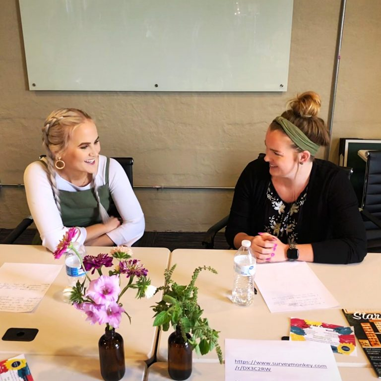 Two women smiling while participating in a business workshop.
