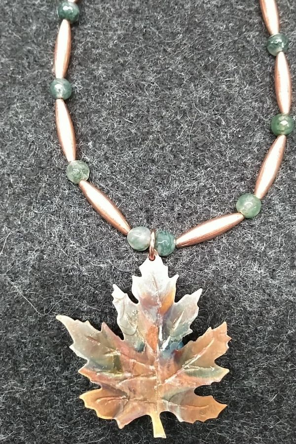 A copper maple leaf pendant on a beaded necklace. Made by Bunny Williams.