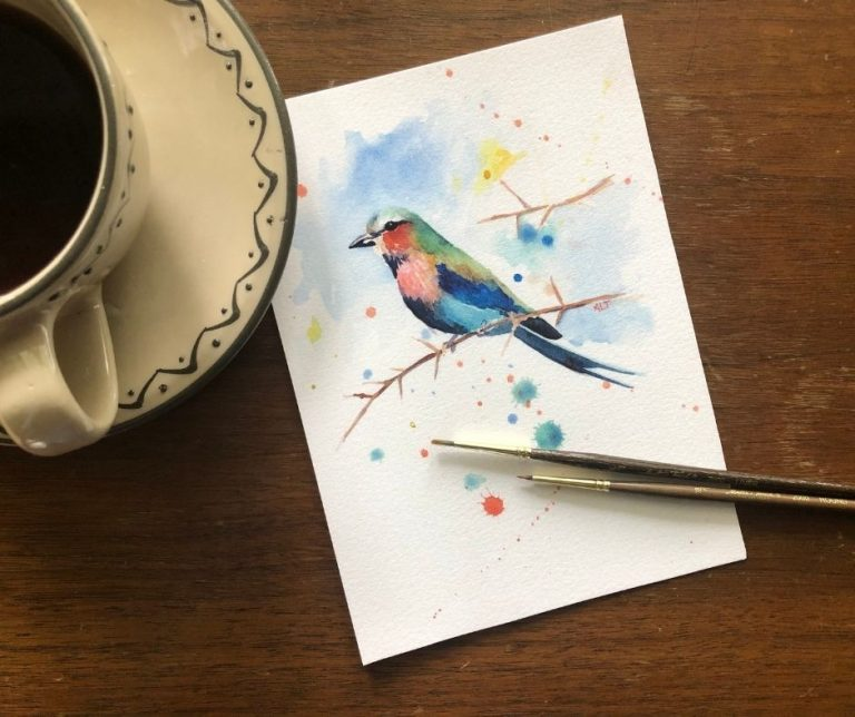 A watercolor print of a colorful bird rests next to a coffee cup and watercolor brushes.