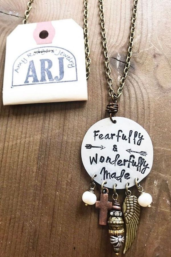 """A pendant necklace with the quote """"fearfully and wonderfully made""""."""