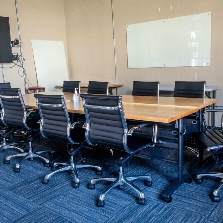 An interior view of the Biz Foundry's Cookeville conference room. A wooden table surrounded by black leather office chairs. There is blue carpeting and a whiteboard on the far wall.