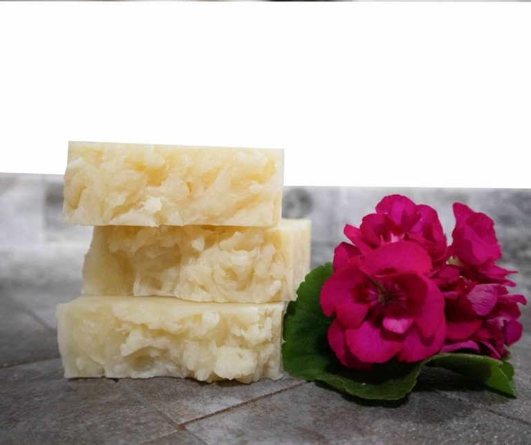 Handmade soaps are stacked next to pink flowers.