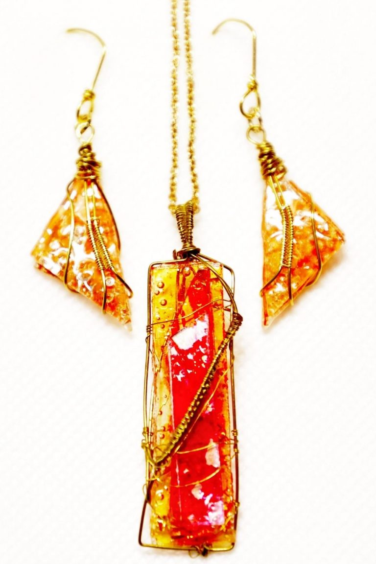A pendant and matching earrings in orange and red. Wrapped in gold wire.